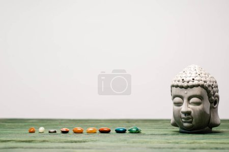 Photo for Buddha statuette and colorful semiprecious stones on wooden surface isolated on grey - Royalty Free Image