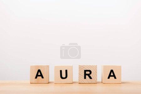 word aura lettering on wooden blocks on white