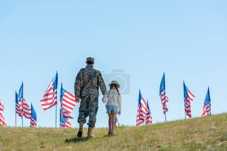 Photo for Back view of father in military uniform holding hands with daughter near american flags - Royalty Free Image