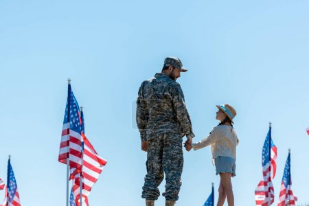 Foto de Padre en uniforme militar que se sostiene de la mano con la hija linda cerca de las banderas americanas - Imagen libre de derechos