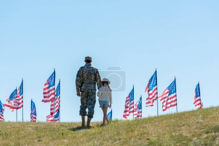 Photo for Back view of father in military uniform holding hands with kid near american flags - Royalty Free Image