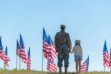 Photo pour Vue arrière du père dans les mains de fixation militaires d'uniforme avec l'enfant près des drapeaux américains - image libre de droit