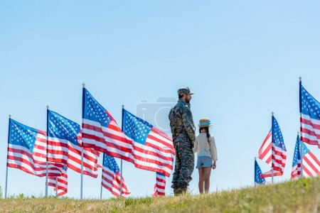 Photo pour Homme en uniforme militaire debout avec sa fille près des drapeaux américains - image libre de droit