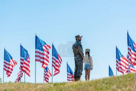 Photo pour Militaire en uniforme debout avec sa fille près des drapeaux américains - image libre de droit