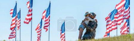 Foto de Disparo panorámico de niño abrazando a su padre en uniforme militar cerca de las banderas americanas - Imagen libre de derechos