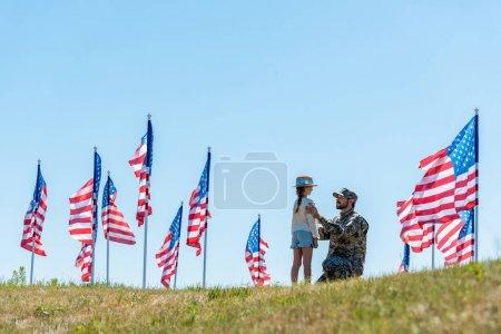 Photo pour Foyer sélectif du père en uniforme militaire regardant la fille près des drapeaux américains - image libre de droit