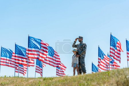 Photo for Selective focus of father in military uniform standing with cute kid near american flags - Royalty Free Image