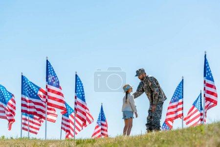 Photo pour Foyer sélectif de l'homme dans l'uniforme militaire regardant la fille près des drapeaux américains - image libre de droit