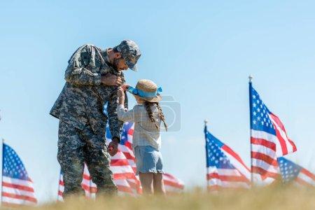 Foto de Enfoque selectivo de niño tocando uniforme de padre militar cerca de banderas americanas - Imagen libre de derechos