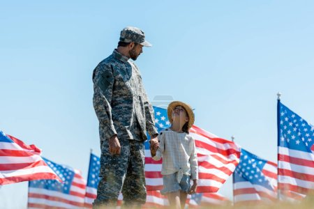 Photo for Selective focus of kid holding hands with military father near american flags - Royalty Free Image