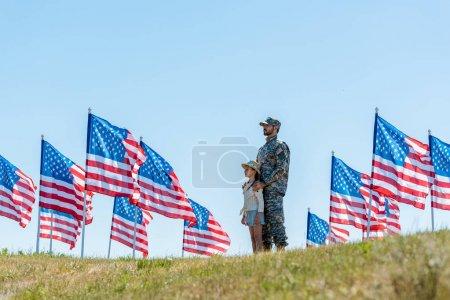 Photo pour Foyer sélectif du père dans l'uniforme militaire restant avec le gosse mignon près des drapeaux américains - image libre de droit
