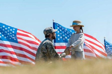 Foto de Enfoque selectivo del padre militar que se está tomando de la mano con el niño feliz cerca de las banderas americanas - Imagen libre de derechos