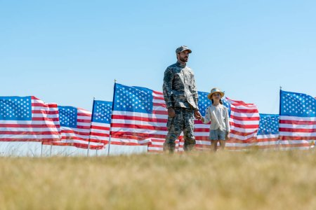 Photo for Selective focus of dad in military uniform holding hands with kid near american flags - Royalty Free Image