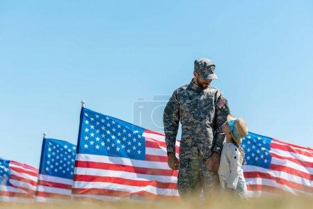 Photo pour Foyer sélectif de l'homme militaire dans la casquette regardant l'enfant et les drapeaux américains - image libre de droit