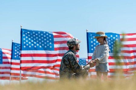 Photo pour Foyer sélectif du père militaire retenant des mains avec le gosse gai près des drapeaux américains - image libre de droit