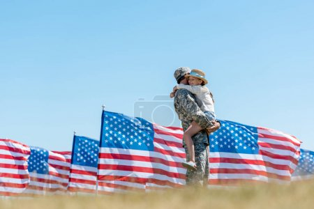 selective focus of military man holding in arms cheerful kid near american flags