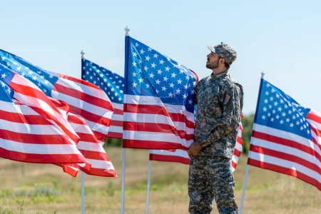 Photo for Man in military uniform and cap standing and touching american flag - Royalty Free Image