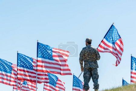 Photo pour Foyer sélectif de l'homme dans l'uniforme militaire et le chapeau restant et retenant le drapeau américain - image libre de droit