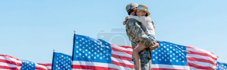Photo pour Panoramic shot of military man holding in arms cheerful child near american flags - image libre de droit