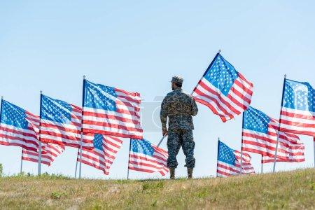 Photo pour Foyer sélectif du soldat dans l'uniforme militaire et le chapeau restant et retenant le drapeau américain - image libre de droit