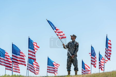 Photo for Selective focus of handsome soldier in military uniform and cap holding american flag - Royalty Free Image