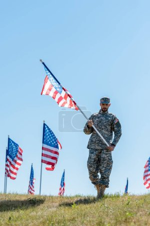 Photo for Handsome soldier in military uniform and cap holding american flag - Royalty Free Image
