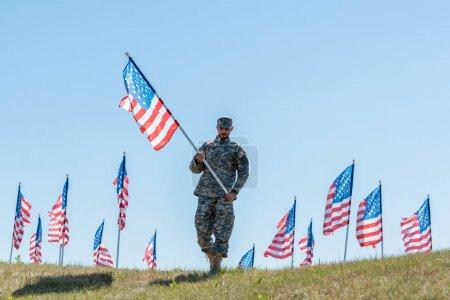 Photo pour Beau soldat dans l'uniforme militaire et le chapeau retenant le drapeau américain tout en restant sur l'herbe - image libre de droit