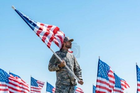 Photo pour Bel homme en uniforme militaire et casquette tenant le drapeau américain tout en se tenant contre le ciel bleu - image libre de droit
