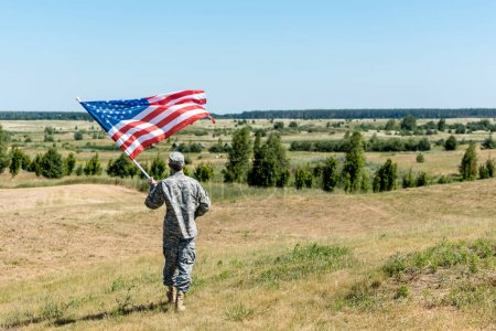 Photo for Military man in uniform standing on grass and holding american flag - Royalty Free Image