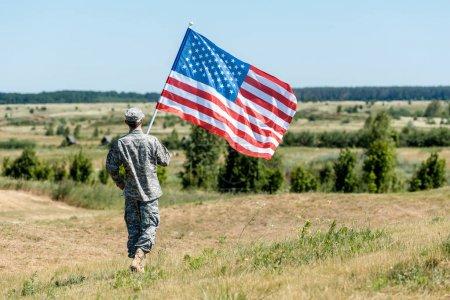 Photo pour Militaire en uniforme marchant sur l'herbe et tenant le drapeau américain - image libre de droit