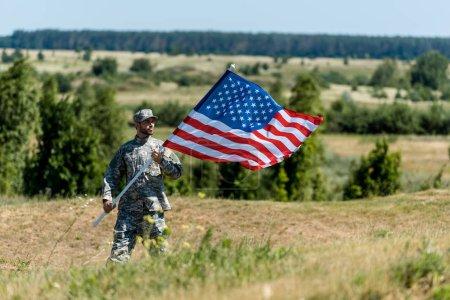 Foto de Enfoque selectivo de hombre militar guapo en uniforme y gorra sosteniendo la bandera americana en verano - Imagen libre de derechos