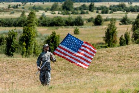 Foto de Enfoque selectivo del hombre militar en uniforme y gorra sosteniendo la bandera americana en verano - Imagen libre de derechos