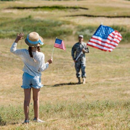 Photo pour Vue arrière de l'enfant dans la main d'ondulation de chapeau de paille tout en retenant le drapeau américain près du père dans l'uniforme militaire - image libre de droit