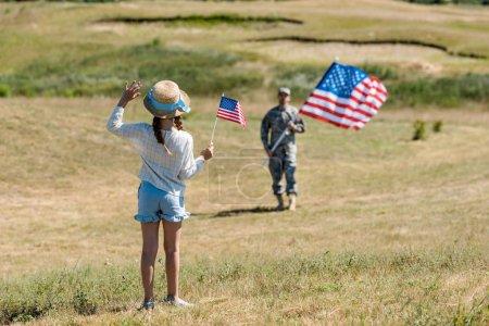 Foto de Vista trasera del niño en sombrero de paja agitando la mano mientras sostiene la bandera americana cerca del padre en uniforme militar - Imagen libre de derechos