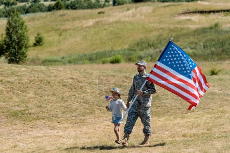 Photo for Military man and happy patriotic kid walking and holding american flags - Royalty Free Image