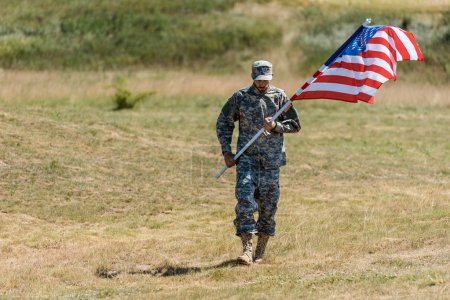 Photo pour Selective focus of soldier walking and holding american flag in summertime - image libre de droit