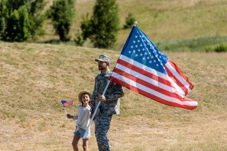 Photo pour Homme militaire et gosse patriotique heureux retenant des drapeaux américains - image libre de droit