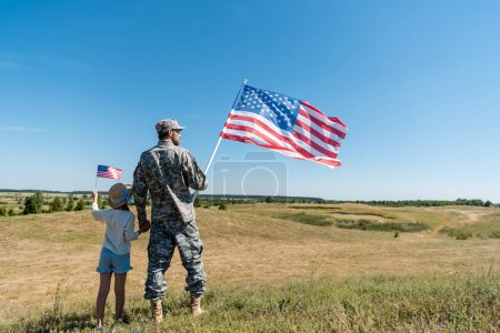Photo for Soldier holding hands with child and holding american flag - Royalty Free Image