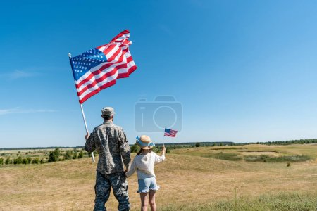 back view of military father and patriotic kid holding american flags