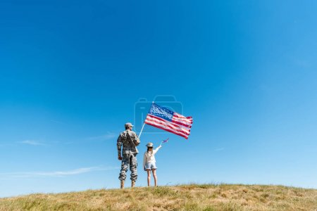 Photo for Back view of kid in straw hat and military father holding american flags - Royalty Free Image