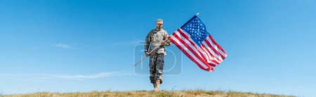 Photo for Panoramic shot of handsome military man in uniform holding american flag with stars and stripes - Royalty Free Image