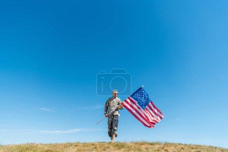 Foto de Guapo militar en uniforme caminando con bandera americana con estrellas y rayas - Imagen libre de derechos