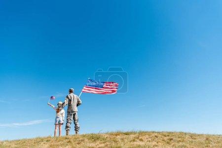 Rückansicht von Kind mit Strohhut und Militärmann mit amerikanischer Flagge