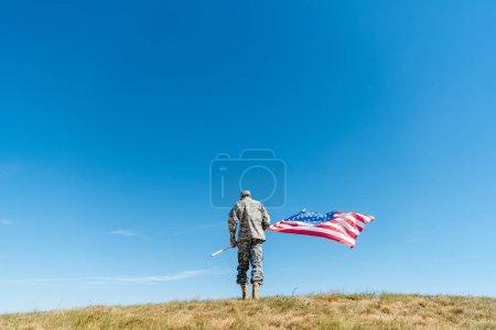 Foto de Vista trasera del militar en uniforme de pie con la bandera americana con estrellas y rayas - Imagen libre de derechos