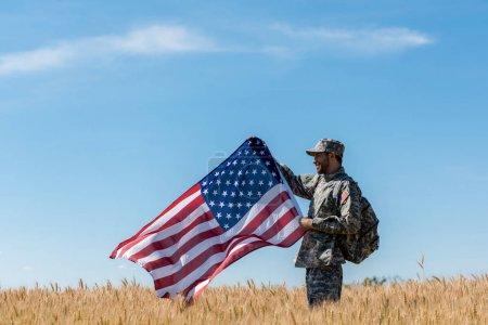 Photo pour Soldat heureux en uniforme militaire debout dans le champ avec du blé doré et tenant le drapeau américain - image libre de droit