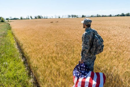 Photo for Handsome man in military uniform holding american flag while standing in field - Royalty Free Image