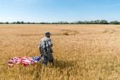 "Постер, картина, фотообои ""handsome man in military uniform holding american flag while standing in field with wheat """