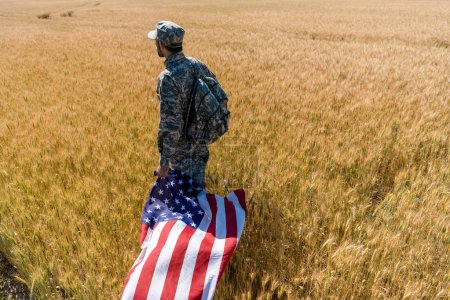 Photo for Soldier in military uniform holding american flag while standing in field with wheat - Royalty Free Image