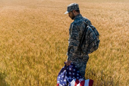 patriotic soldier in military uniform holding american flag while standing in field with wheat
