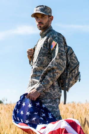 Photo for Selective focus of soldier in uniform holding american flag while standing in field - Royalty Free Image